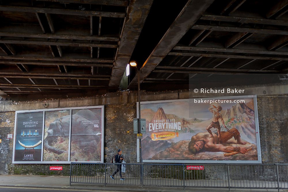 The quirky juxtaposition of a billboards for stopping the hunting of elephant for the ivory trade, and energy drink brand Lucozade, at Elephant And Castle, on 3rd May 2018, in south London, UK.