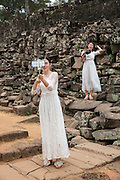A Chinese women take a selfie photo from her phone dressed in white bridal dresses standing by the ancient ruins of Angkor Thom, Siem Reap Province, Cambodia, South East Asia. A second woman, also dressed as a bride, stands on the stone wall with a DSLR camera.  (photo by Andrew Aitchison / In pictures via Getty Images)