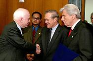 Senator John McCain shakes hand with Secretary of Defense Donald Rumsfeld  as Senator John Warner looks on before the start of the  Senate Armed Services Committee on allegations of mistreatment of Iraqi prisoners on May 7, 2004.  Photo by Dennis Brack