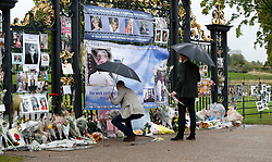 The Duke of Cambridge leaves flowers as he and Prince Harry look at tributes to Diana, Princess of Wales attached to the Golden Gates of Kensington Palace, London, ahead of the 20th anniversary of their mother's death.
