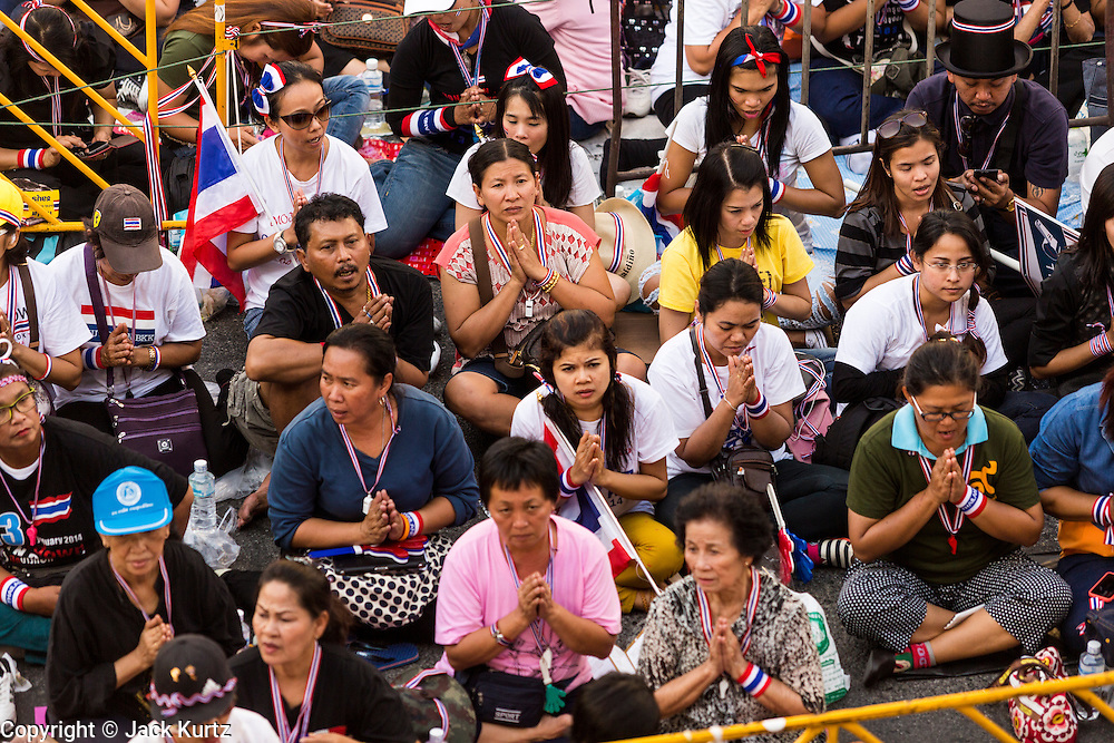 """13 JANUARY 2014 - BANGKOK, THAILAND: Anti-government protestors pray in the Asok intersection in Bangkok. Tens of thousands of Thai anti-government protestors took to the streets of Bangkok Monday to shut down the Thai capitol. The protest was called """"Shutdown Bangkok"""" and is expected to last at least a week. The Shutdown Bangkok protest is a continuation of protests that started in early November. There have been shootings almost every night at different protests sites around Bangkok, including two Sunday night, but the protests Monday were peaceful. The malls in Bangkok stayed open Monday but many other businesses closed for the day and mass transit was swamped with both protestors and people who had to use mass transit because the roads were blocked.    PHOTO BY JACK KURTZ"""