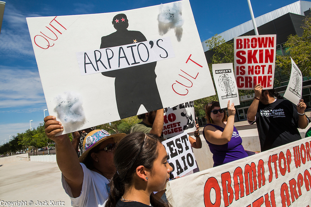"""19 JULY 2012 - PHOENIX, AZ: Members of  Puente, a human rights organization, rally against Maricopa County Sheriff Joe Arpaio in front of the US Courthouse on the first day of a class action lawsuit, Melendres v. Arpaio in Phoenix Thursday. The suit, brought by the ACLU and MALDEF in federal court against Maricopa County Sheriff Joe Arpaio, alleges a wide spread pattern of racial profiling during Arpaio's """"crime suppression sweeps"""" that targeted undocumented immigrants. U.S. District Judge Murray Snow granted the case class action status opening it up to all Latinos stopped by Maricopa County Sheriff's Office deputies during the crime sweeps. The case is being heard in Judge Snow's court.   PHOTO BY JACK KURTZ"""