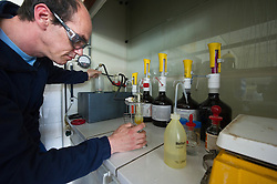 Chemist Thomas Pauwels,  breaks down the liquid chlorine into its base chemical components to determine the concentration of bromides in the liquid chlorine. The red glow in the base of the beaker shows the chemical reaction in progress, at the Solvay SA chemical plant in Antwerp, Belgium, on Thursday, April 22, 2010.  Solvay SA is the world's largest supplier of Soda Ash or Sodium Carbonate and is also a major producer of caustic soda, hydrogen peroxide, chlorine and fluorinated products. (Photo © Jock Fistick)