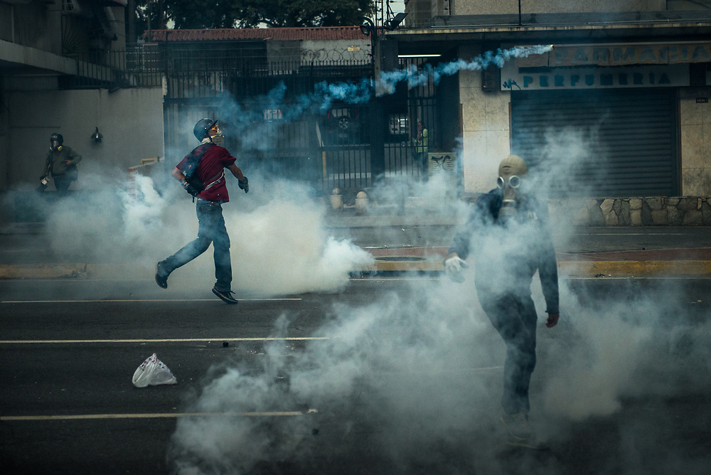 CARACAS, VENEZUELA - MAY 22, 2017: Anti-government protesters throws a tear gas canister back at members of the National Police, who had previously shot it at a group of protesters during clashes in Caracas. The streets of Caracas and other cities across Venezuela have been filled with tens of thousands of demonstrators for nearly 100 days of massive protests, held since April 1st. Protesters are enraged at the government for becoming an increasingly repressive, authoritarian regime that has delayed elections, used armed government loyalist to threaten dissidents, called for the Constitution to be re-written to favor them, jailed and tortured protesters and members of the political opposition, and whose corruption and failed economic policy has caused the current economic crisis that has led to widespread food and medicine shortages across the country.  Independent local media report nearly 100 people have been killed during protests and protest-related riots and looting.  The government currently only officially reports 75 deaths.  Over 2,000 people have been injured, and over 3,000 protesters have been detained by authorities.  PHOTO: Meridith Kohut