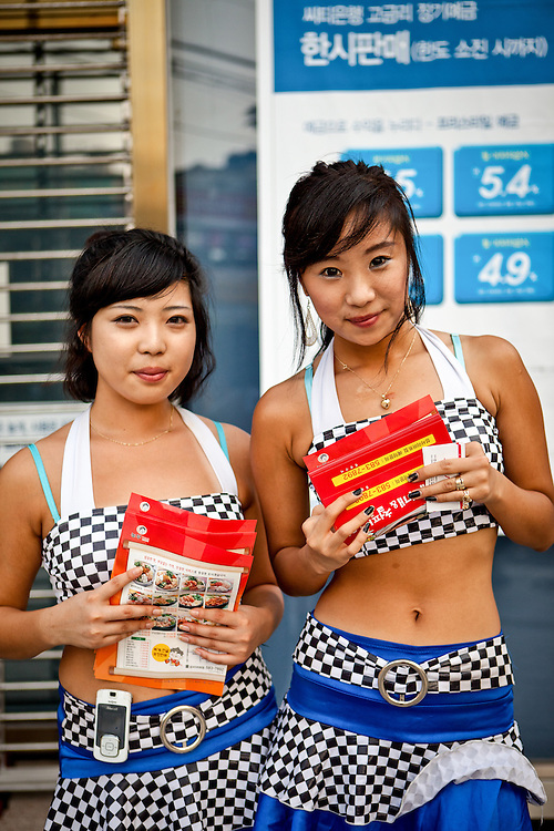 Portrait of two young students handing out flyers for a company in the city of Daegu, South Korea.