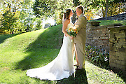 Bride and groom on backlit, sunlit hillside next to a stone wall, The Majors Inn, Gilbertsville, NY