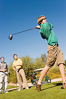 Golfer Teeing Off While Friends Watch