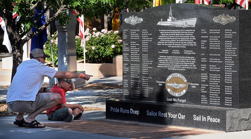 jt052917d/ a sec/jim thompson/Jason Davis and his son Jacob-9 were having a bit of a civic lesson as they check out one of the many memorial monuments at the Memorial Day Ceremony held at the New Mexico Veteran's Memorial. Monday May. 29, 2017. (Jim Thompson/Albuquerque Journal)