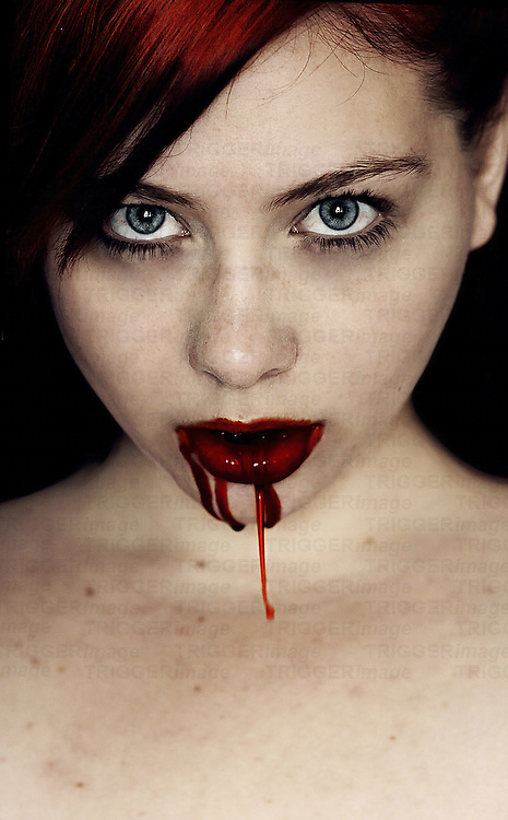 A young woman with blood dripping from her mouth staring at the camera.