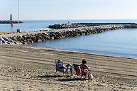 Spain, Malaga Province, Puerto Banus, two visitors, deck chairs, sunbathing, almost deserted beach, December, 2018, 201812100131<br />