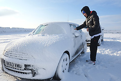 &copy; Licensed to London News Pictures. <br /> 27/12/2014. <br /> <br /> Castleton, United Kingdom.<br /> <br /> A man clear snow from his car near The Lion Inn on the North Yorkshire Moors near Castleton after overnight snowfall caused disruption in some parts of the country.<br /> <br /> Photo credit : Ian Forsyth/LNP