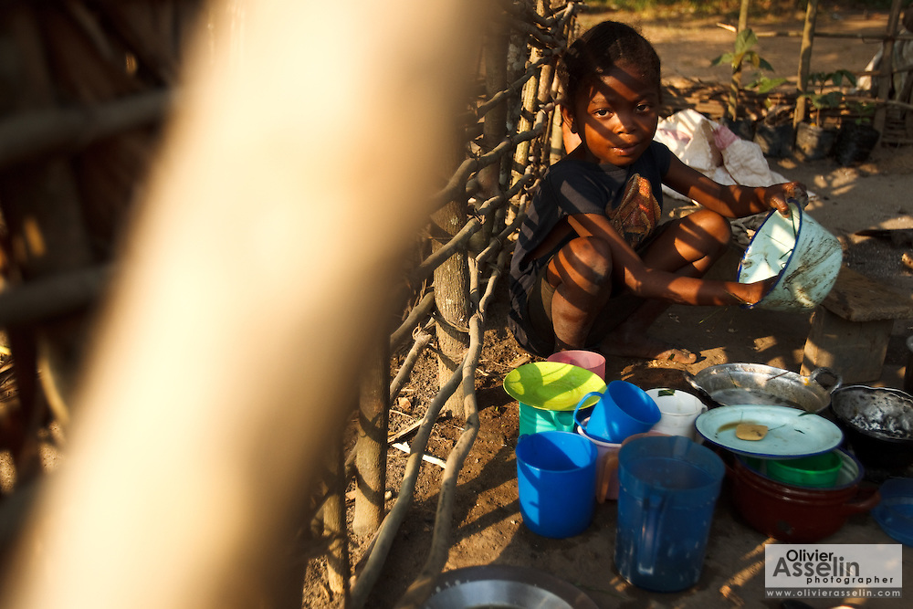 A young girl does dishes outside her home in the village of Kilau, Bas-Congo province, Democratic Republic of Congo on Monday June 20, 2011. The village was certified a healthy village as part of the unicef-sponsored programme..
