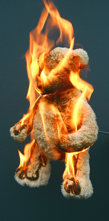 A child's toy bear (teddy bear) set alight and in flames. Toys are made of fire retardant fabrics