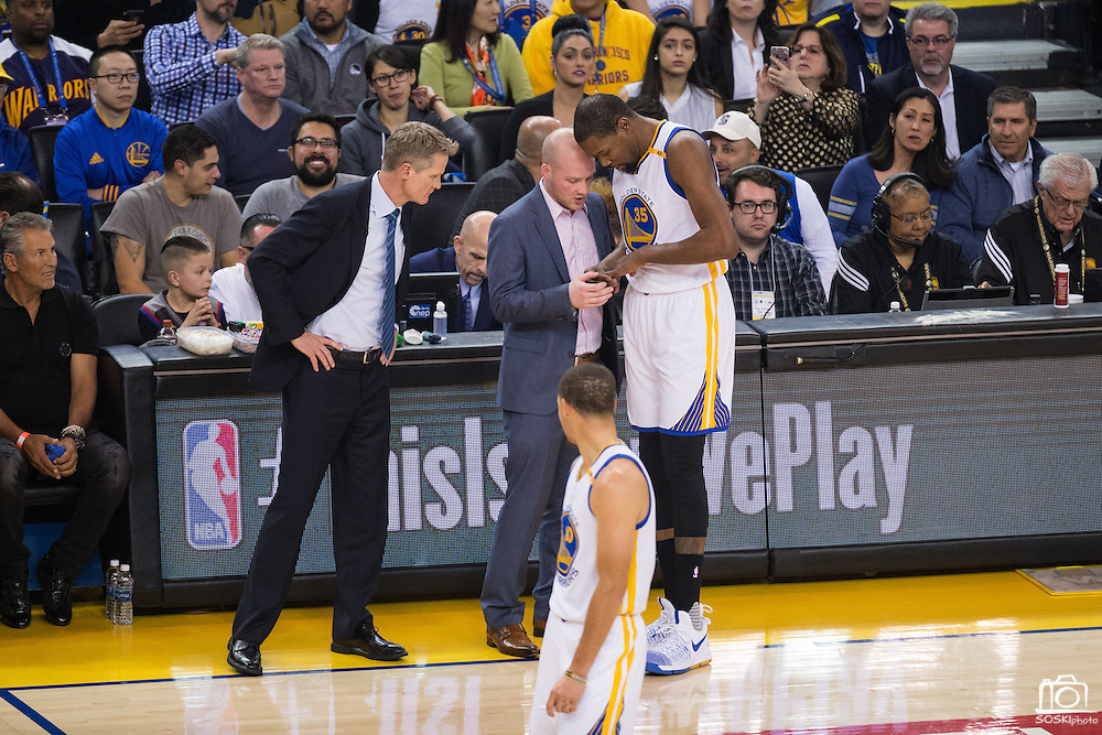 Golden State Warriors head coach Steve Kerr and a trainer check out Golden State Warriors forward Kevin Durant (35) in between plays against the LA Clippers at Oracle Arena in Oakland, Calif., on February 23, 2017. (Stan Olszewski/Special to S.F. Examiner)