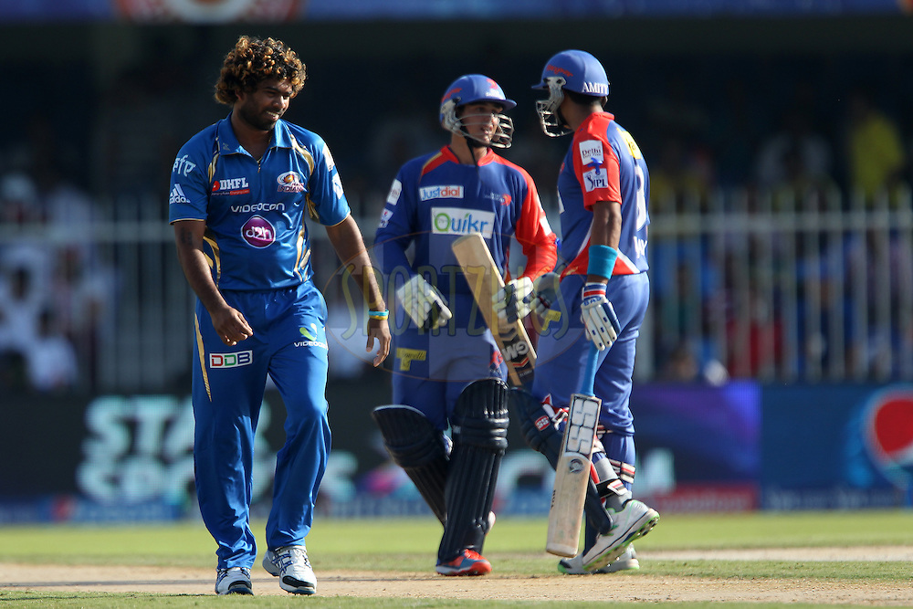 Lasith Malinga of the Mumbai Indians smiles as Quinton de Kock of the Delhi Daredevils and Murali Vijay of the Delhi Daredevils celebrate the four during match 16 of the Pepsi Indian Premier League 2014 between the Delhi Daredevils and the Mumbai Indians held at the Sharjah Cricket Stadium, Sharjah, United Arab Emirates on the 27th April 2014<br /> <br /> Photo by Ron Gaunt / IPL / SPORTZPICS