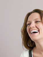Mid-adult woman looking away and laughing close-up