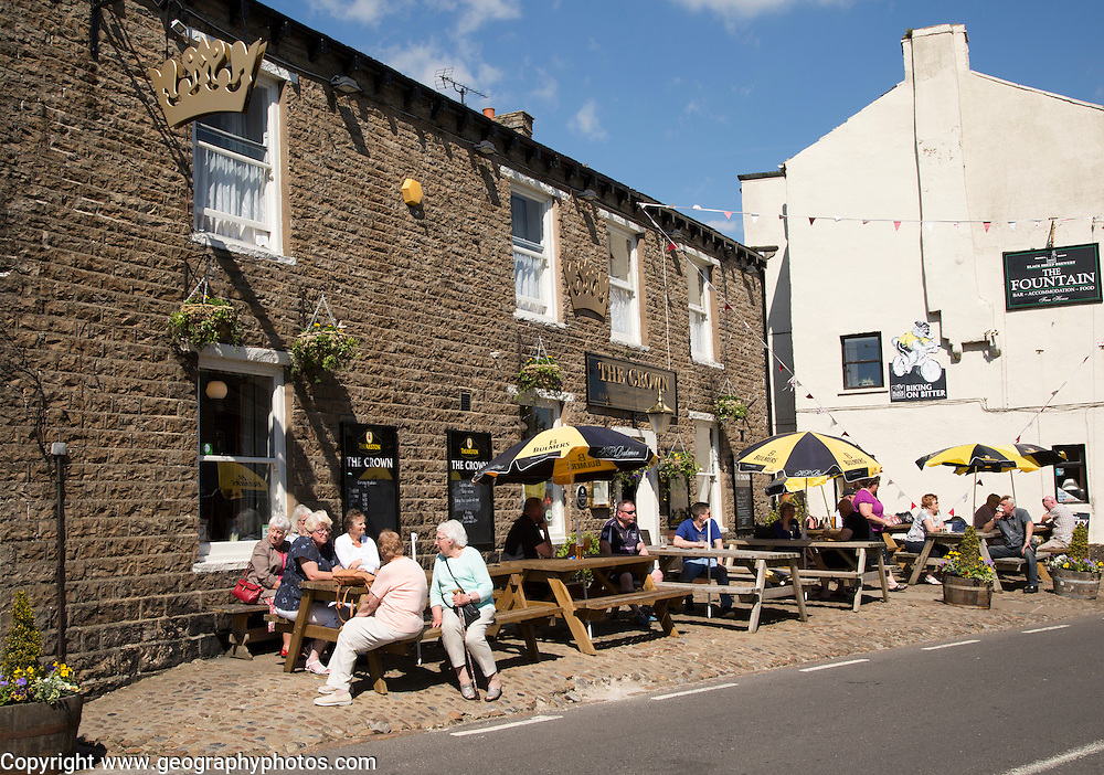 People sitting outside pubs in the village of Hawes, Yorkshire Dales national park, England, UK