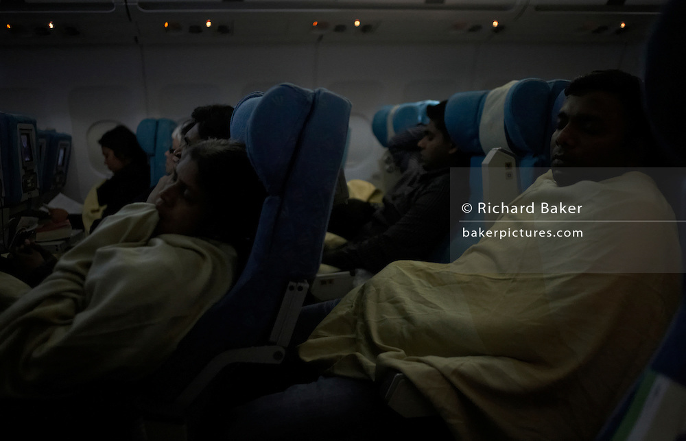 With cabin lights dimmed, economy class passengers sleep under blankets on an international long-haul flight