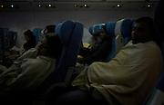 With cabin lights dimmed, economy class passengers sleep under blankets on an international long-haul flight