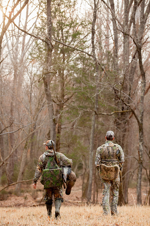 Two friends walking through a field while turkey hunting.