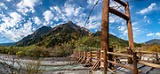 """Myojin bridge over the Azusa River. Kamikochi (""""Upper Highlands"""") is a high valley within the Hida Mountains, in Chubu-Sangaku National Park, Nagano Prefecture, Japan. Last logged in the mid 1800s, it is now a popular nature resort. Embraced within the """"Northern Alps"""" of the Japanese Alps, the valley floor ranges from 1400 m (4600 ft) to 1600 m (5200 ft) elevation. Its highest peak is Okuhotakadake (3190 m or 10,470 ft). This image was stitched from multiple overlapping photos."""