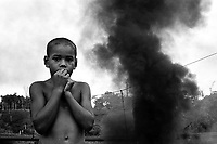 A young boy stands in front of an oil pipeline that was blown up during an attack by rebels of the Revolutionary Armed Forces of Colombia, or FARC, in the Putumayo, a coca-growing region in southern Colombia. (Photo/Scott Dalton)
