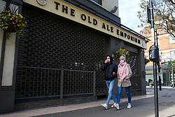 © Licensed to London News Pictures. 21/03/2020. London, UK. People with face masks walk past closed a pub in Green Lanes, Haringey, north London. The closures follow Prime Minister, BORIS JOHNSON'S request that all restaurants, cafes and pubs should close until further notice as the Coronavirus impact worsens. Photo credit: Dinendra Haria/LNP