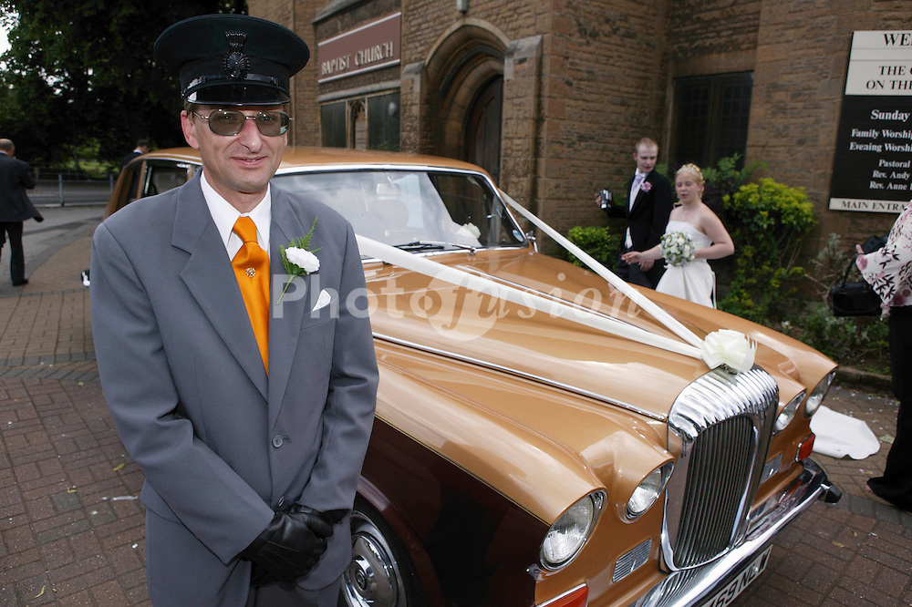 Chauffeur standing by wedding car with bride and groom in background,