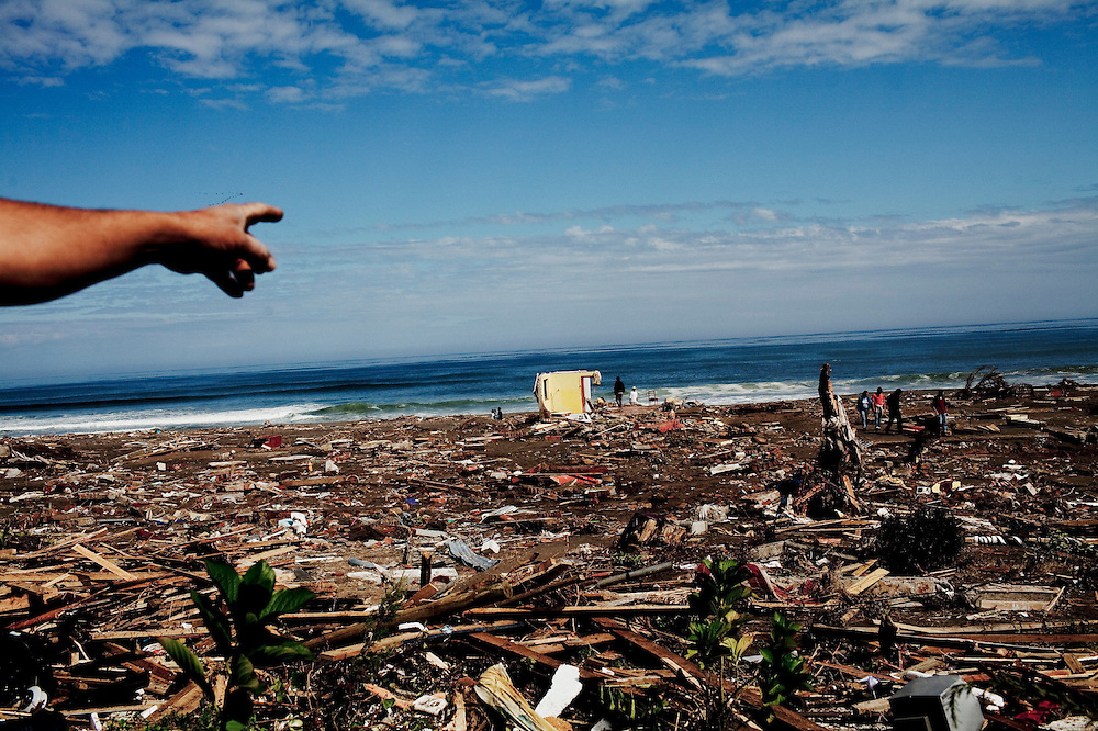 A neighbor points to a residential area completely devastated by the tsunami in Pelluhue, March 2, 2010. The February 27 8.8-magnitude quake that hit Chile was so strong it triggered a Pacific-wide tsunami that affected 200 kilometers of coastline, at places sweeping 2,000 meters inland. It killed more than 400 people.