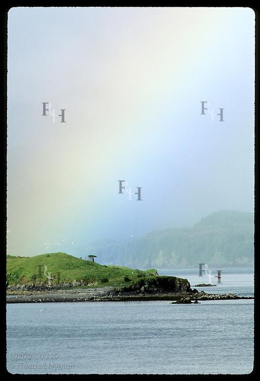 Wide rainbow soars skyward behind Puffin Island in Chiniak Bay on misty July morn; Kodiak Island. Alaska