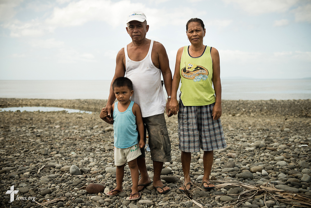 A family who nearly lost their home during Typhoon Haiyan poses for a portrait against the water near the Awit Strait in Mayahag, Leyte Province, Philippines, on Saturday, March 15, 2014. Help from LCMS disaster dollars helped them rebuild their home following the storm. LCMS Communications/Erik M. Lunsford