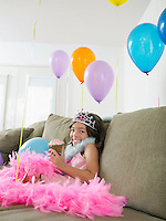 Young girl (7-9) sitting on sofa with balloons eating cupcake