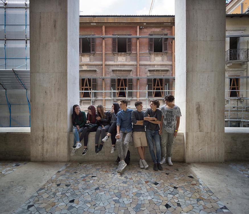 Adolescenti seduti su un muretto del centro della citt&agrave; di Aquila, sotto i portici di Via San Bernardino.<br /> Teenagers sitting on a low wall in the center of the city of Aquila, San bernardino street