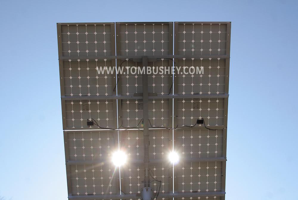 Chatham, NY - Sunlight shines through an array of photovoltaic modules at Sundog Solar on Nov. 21, 2008.