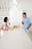 Couple eating breakfast at kitchen bench side view