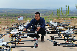 April 25, 2017 - Captain of the flying team checks drones before taking off in Jixian County, north China's Shanxi Province. Over 50,000 mu (3,333 hectares) of apple trees will be sprayed pesticide with drones this year.  (Credit Image: © Cao Yang/Xinhua via ZUMA Wire)