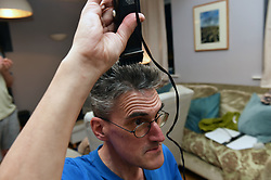 Life in coronavirus lockdown in the UK April 2020. Man having to cut his hair himself using clippers.  Model released.