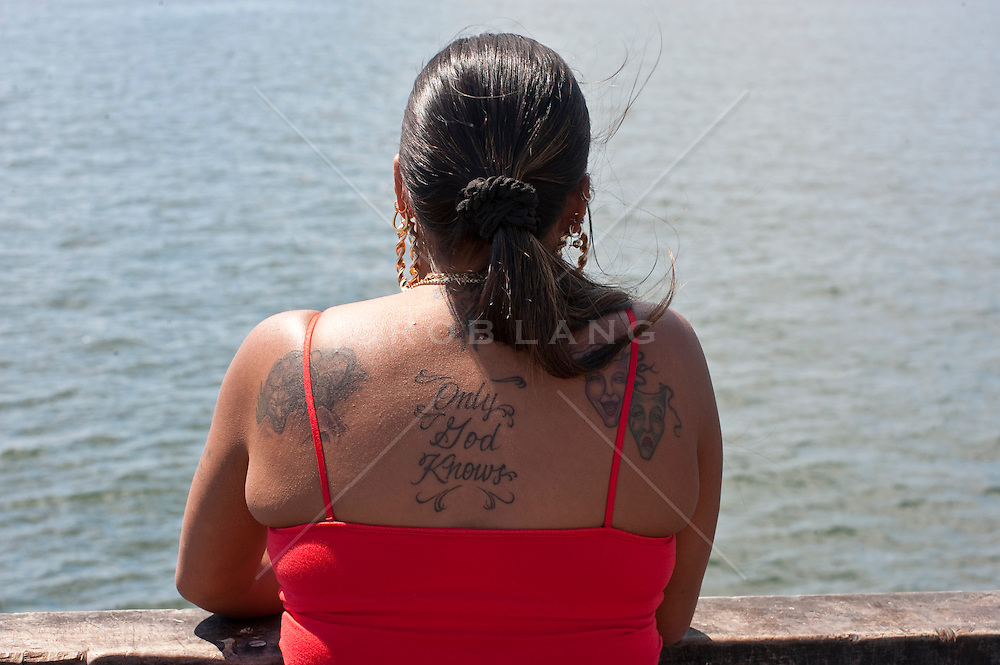 tattooed woman looking out at the water on Coney Island, NY