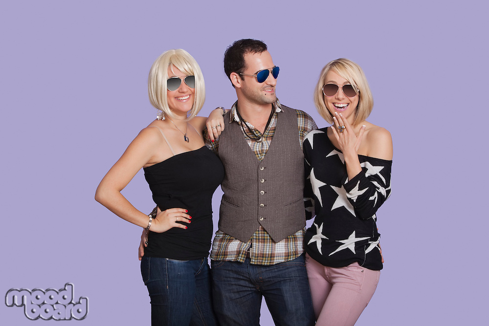 Portrait of young man with two beautiful women over purple background