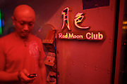Sanlitun bar street nightlife district. Red Moon Club. Man with mobile phone.
