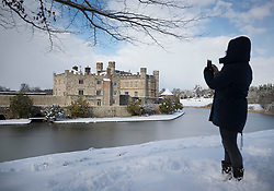 © Licensed to London News Pictures. 27/02/2018. Leeds Castle, UK. A walker takes a photo of Leeds Castle after heavy snow closed it for the day. Freezing temperatures and heavy snow are affecting large parts of Kent.  Photo credit: Peter Macdiarmid/LNP