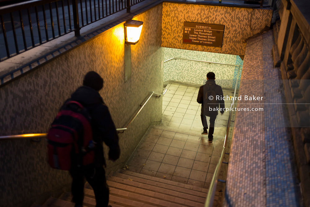 A man follows another into the foot tunnel under London Bridge during the evening rush-hour, on 8th November 2018, in London, England.