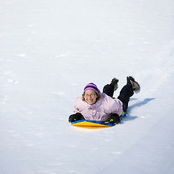 A woman rides her sled down a  hill in Quechee, Vermont.