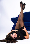 Young lady in seductive pose showing her legs in front of a blue sofa