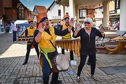 An enthusiastic Linda from Wickford is persuaded to join in with the colourful musicans of La Complet' Mandingue in South Woodham ferrers Town centre.