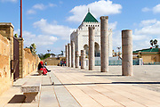 RABAT, MOROCCO - 27th May 2014 - Tourists sit on a bench outside the entrance of the Mausoleum of Mohammed V in Yacoub al-Mansour esplanade in Rabat, Morocco.