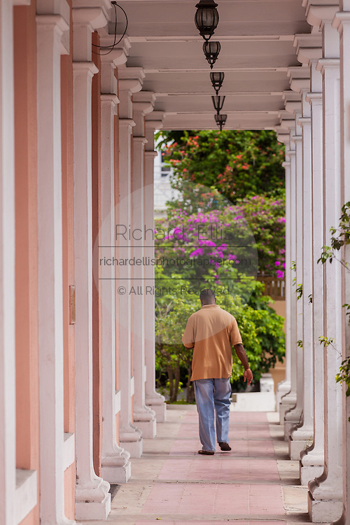 A man walks through the colonnade of a government building in Parliament Square Nassau, Bahamas.