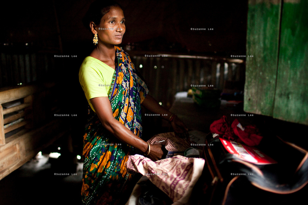 Shahida Begum, 35, looks out the window as she organises her products in her hut in Palashbari Villlage, Taragonj, Rangpur, Bangladesh on 18th September 2011, after a regular day of work as a saleswoman earning 3500 - 5000 Bangladeshi Taka per month. She is one of many rural Bangladeshi women trained by NGO CARE Bangladesh as part of their project on empowering women in this traditionally patriarchal society. Named 'Aparajitas', which means 'women who never accept defeat', these women are trained to sell products in their villages and others around them from door-to-door, bringing global products from brands such as BATA, Unilever and GDFL to the most remote of villages, and bringing social and financial empowerment to themselves.  Photo by Suzanne Lee for The Guardian