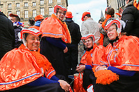 30th April 2013 Amsterdam, Netherlands. Dam Square. Queen Beatrix' abdication takes place, and her son Prince Willem-Alexander will be King of the Netherlands. Women from Staphorst in traditional self made clothes laugh are waiting for the arrival of the  new King on the balcony in front of the royal palace.