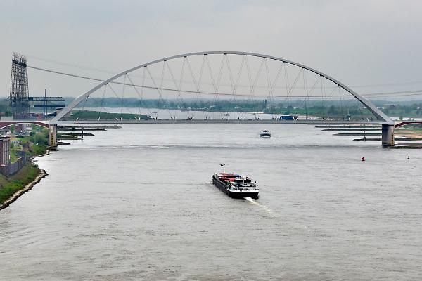 Nederland, Nijmegen, 18-12-2017Binnenvaartschepen, varen over de Waal  en langs de Nevengeul, spiegelwaal . Daar waar de brug de Oversteek ligt eindigt de hoogwatergeul .FOTO: FLIP FRANSSEN
